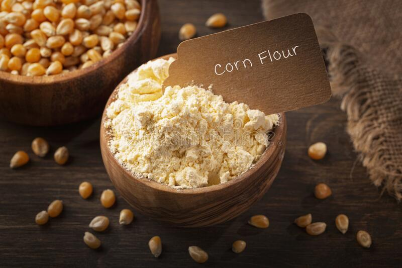 Corn flour in a wooden spoon royalty free stock images