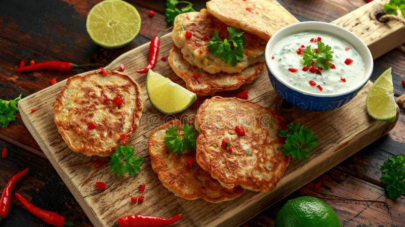 Corn fritters, pancake with dip white sauce, lime and chilli on wooden board royalty free stock photo