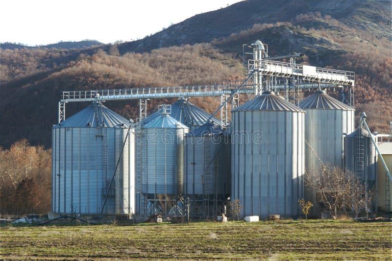 Corn grain silo tanks warehouse plant. Mountains background stock images