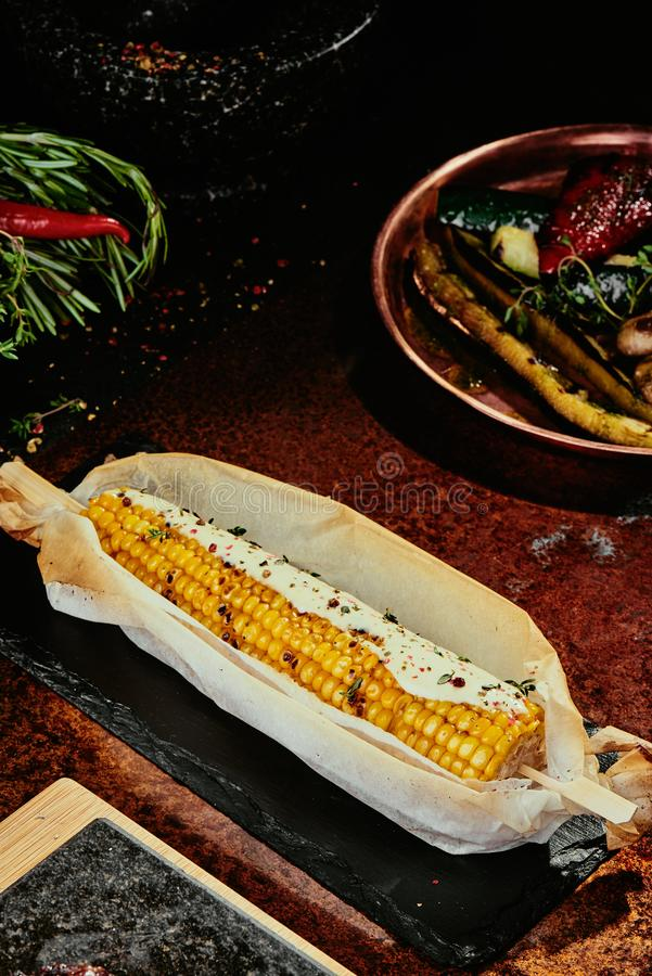 Corn grilled on a black stone plate on a copper background stock photo