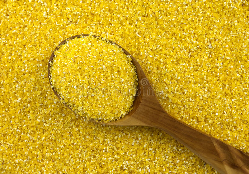 Corn grits coarsely ground with wooden spoon royalty free stock photography