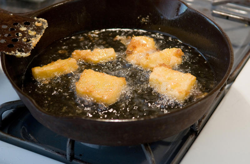 Corn meal mush. Frying in oil - a traditional American regional (and soul food) dish for breakfast or anytime stock photos