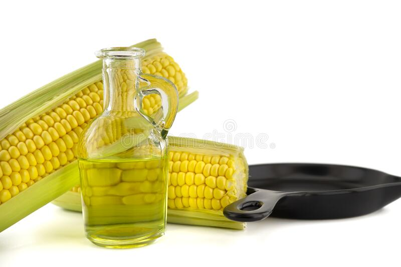 Corn oil in decanter and fresh corncobs. Next to the cast iron skillet isolated on white background with free copy space for text royalty free stock images