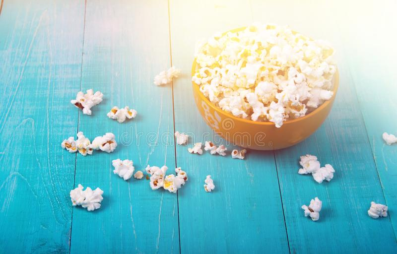 Corn popcorn on a blue wooden background, as a snack for watching movies stock photos