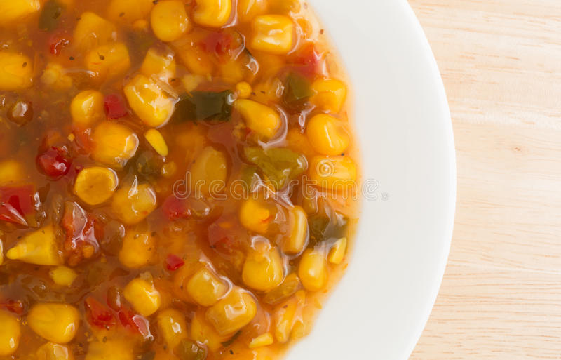 Corn relish in a white dish top view. Top close view of a white dish with corn relish on a wood table top illuminated with natural light royalty free stock images