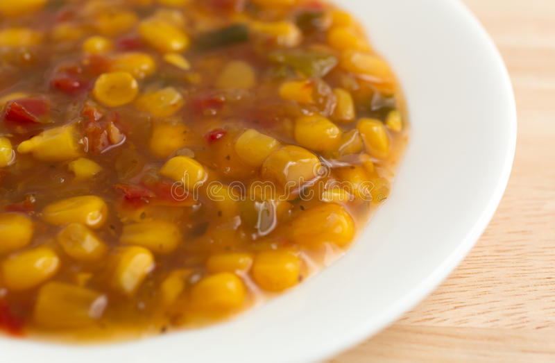 Corn relish in a white dish. A white dish with corn relish on a wood table top illuminated with natural light stock photo