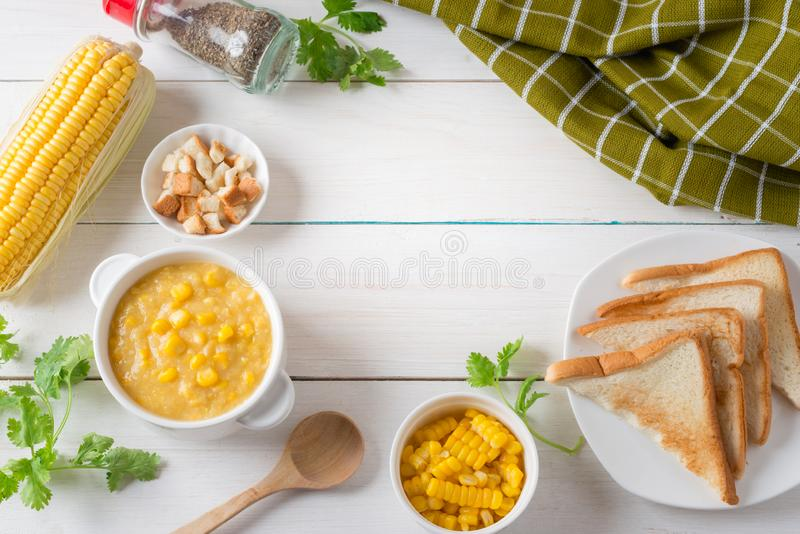 Corn soup in white bowl and crispy bread, toast corn with pepper on white table. Top view with Copy space stock image