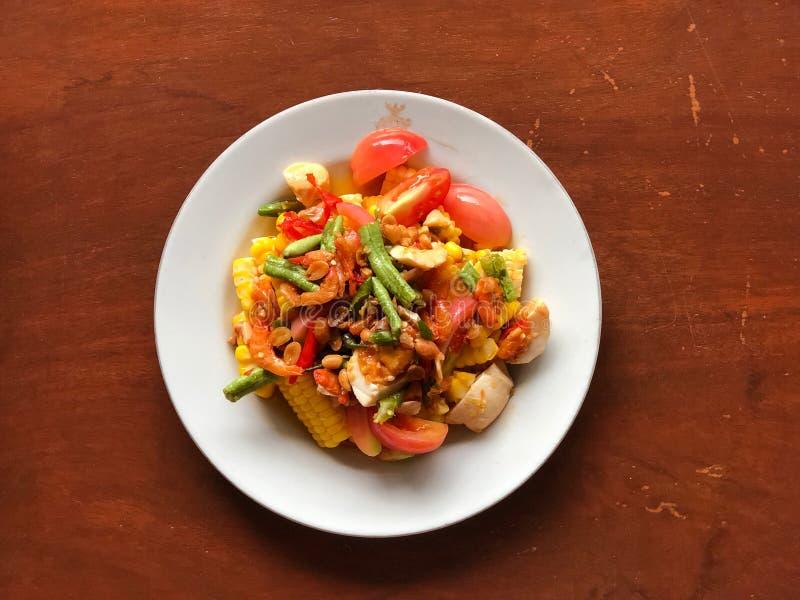 Corn Spicy salad met ei in wit schaaltje op houten tafel Thaise traditionele en populaire levensmiddelen royalty-vrije stock afbeeldingen