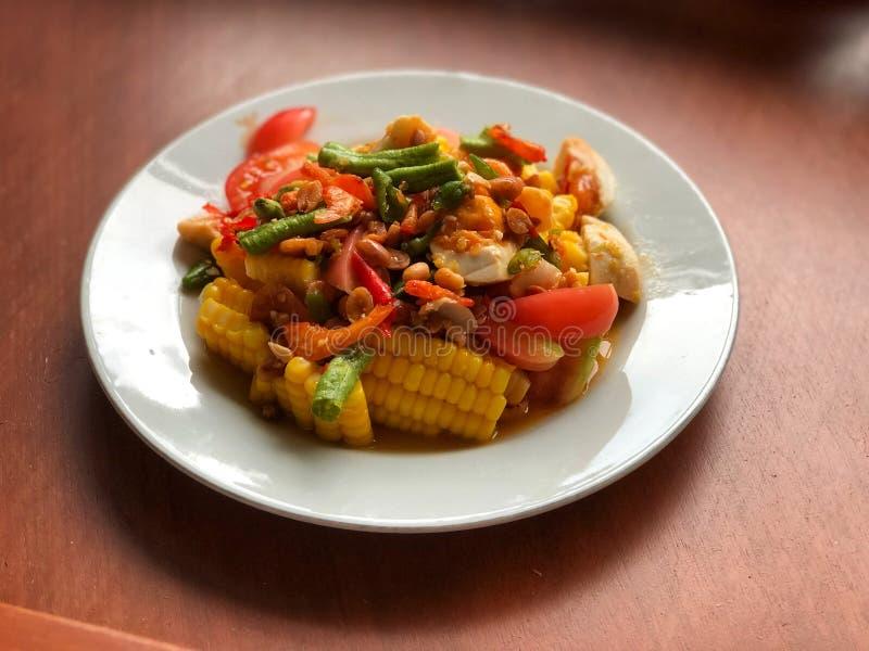 Corn Spicy salad met ei in wit schaaltje op houten tafel Thaise traditionele en populaire levensmiddelen stock foto's