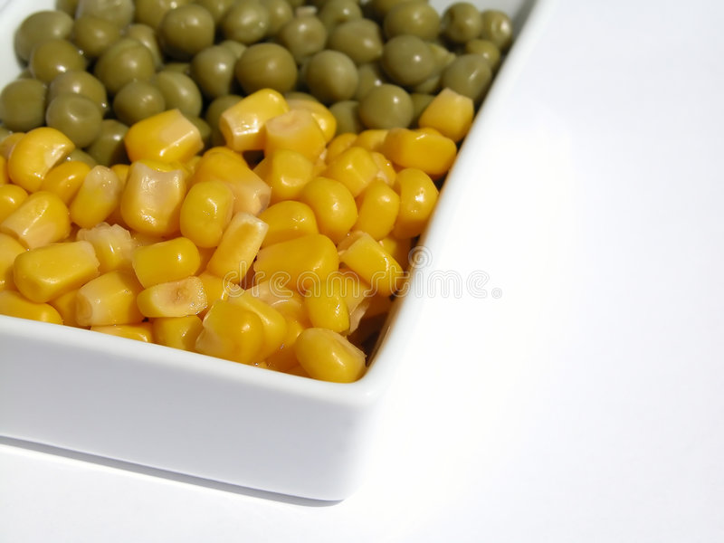 Corn and sweet pea. On white plate royalty free stock photography