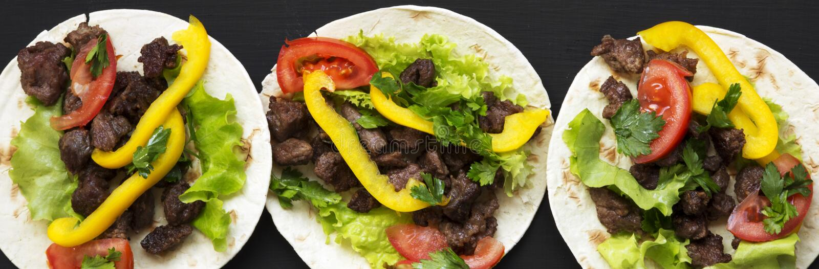 Corn tortillas with beef and vegetables on black background, top view. Mexican cuisine. Flat lay, from above royalty free stock photo