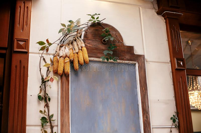 Corn on wooden board with space for text in city street, holiday autumnal decoration of store fronts. Halloween street decor. royalty free stock photo