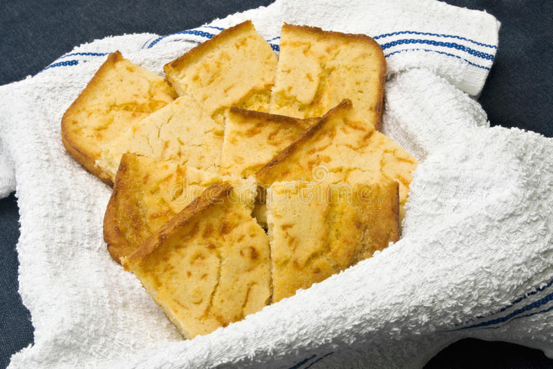 Cornbread. Homemade cornbread served on a clean new dish towel. Dark blue denim fabric background royalty free stock image