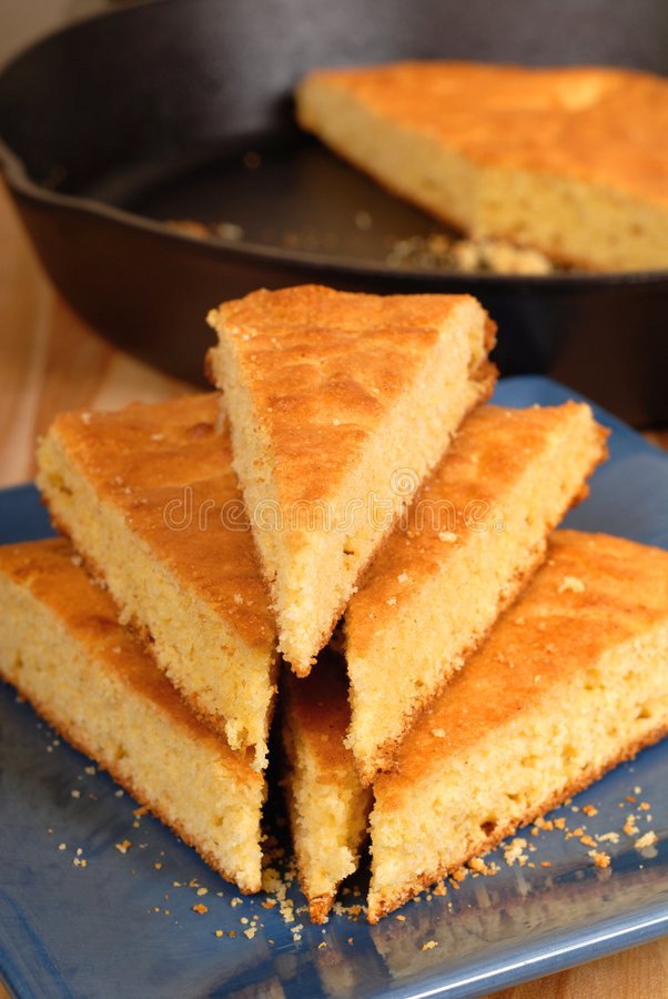 Cornbread on blue plate. A stack of cornbread on blue plate with black skillet in background royalty free stock image