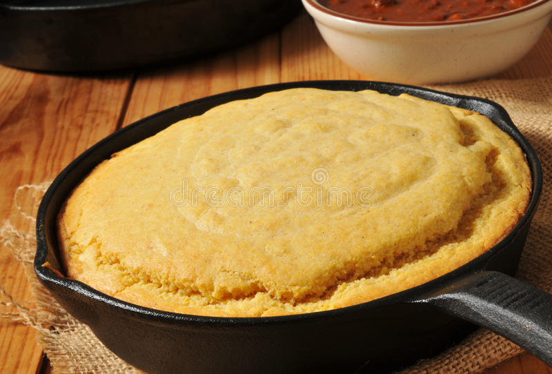 Cornbread and chili. Cornbread in a cast iron skillet with a bowl of chili stock photos