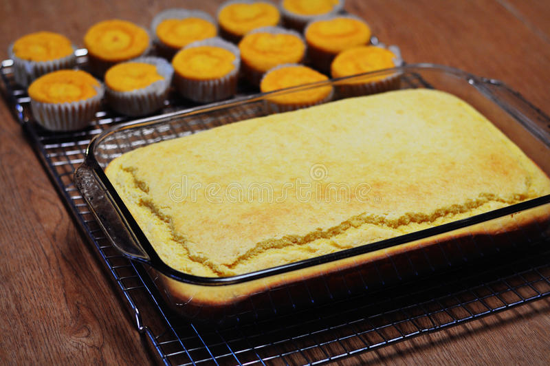 Cornbread. A cooling rack with a 9x13 pan of cornbread along with some cornbread muffins off in the background on baking day royalty free stock image