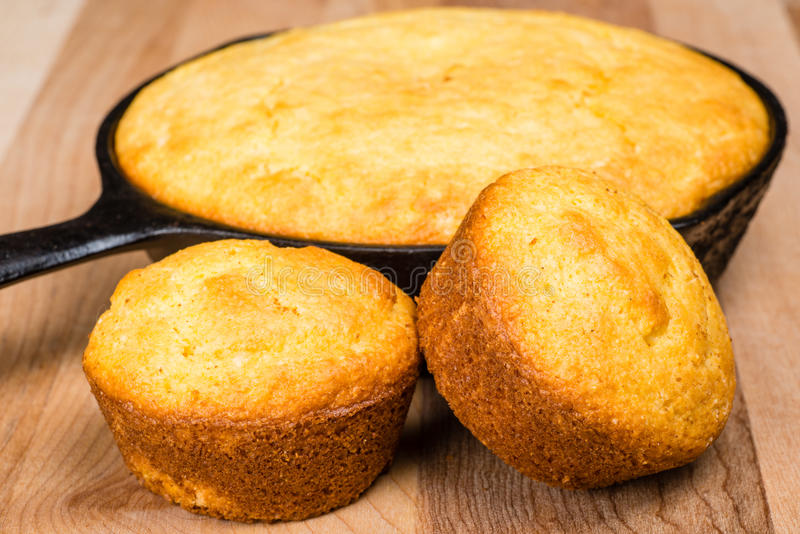 Cornbread muffins and cornbread pone. In an iron skillet royalty free stock photography