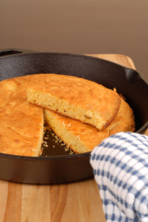 Cornbread in skillet. Cornbread in a cast iron skillet with piece cut out vertical view royalty free stock photo