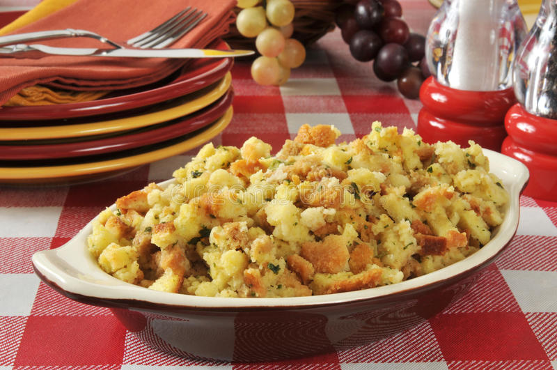 Cornbread stuffing. A casserole dish of cornbread stuffing with plates in the background stock image