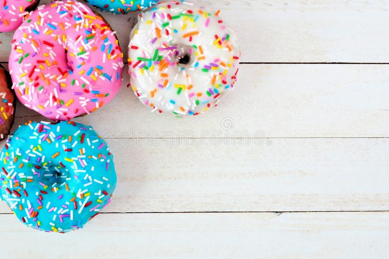 Corner border of assorted donuts with pastel icing against white wood royalty free stock photography