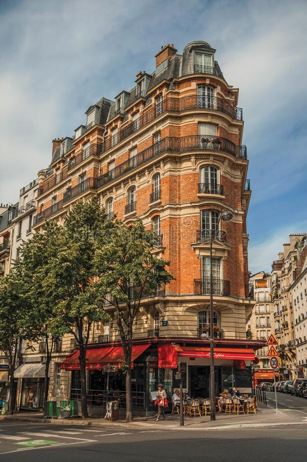 Corner brick building with restaurant and trees in Paris. royalty free stock photo