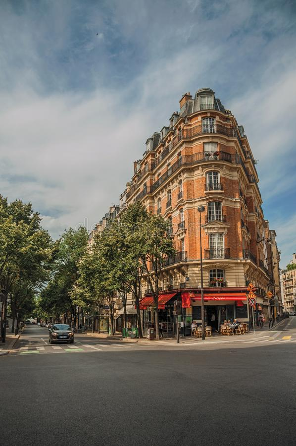 Corner brick building with restaurant and trees in Paris. Paris, northern France - July 09, 2017. Corner brick building with restaurant and trees in Paris stock photography