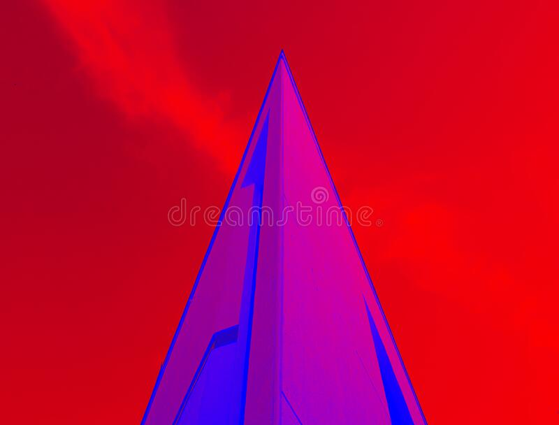 The corner of the building, a triangle protruding upwards in purple on a red background. stock photography