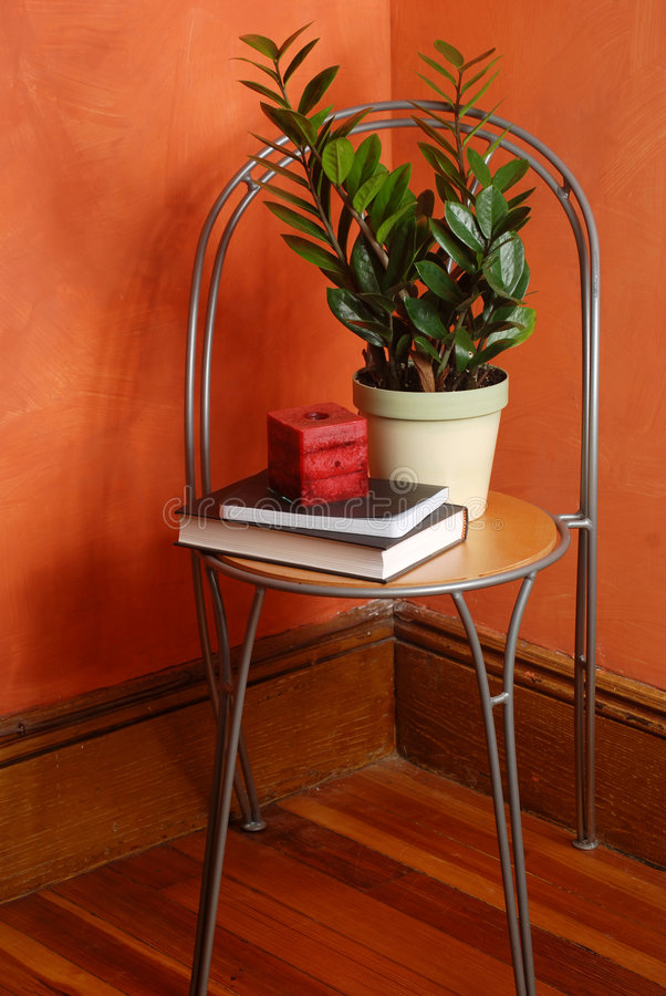 Corner chair. Candle, plant and books on a modern chair in a room corner stock photography