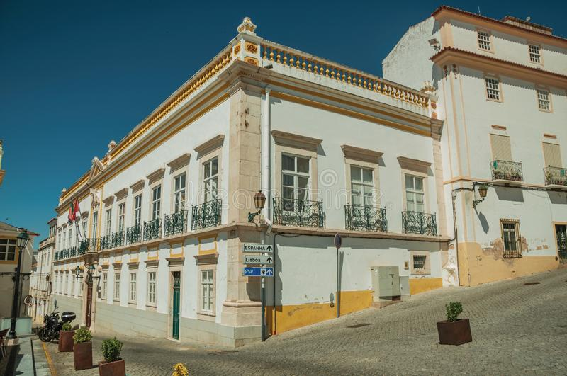 Corner of colorful house with big windows and iron balconies. On a deserted square in a sunny day at Elvas. A gracious star-shaped fortress city on the royalty free stock photography