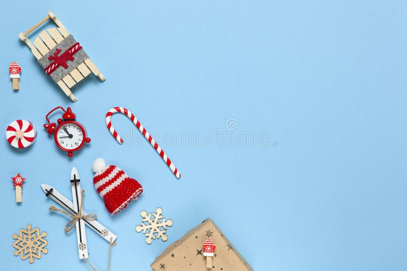 Corner creative Christmas composition. Candy cane, gift in craft paper, sled with deer, hat, alarm clock, ski, clothespins, wooden royalty free stock images