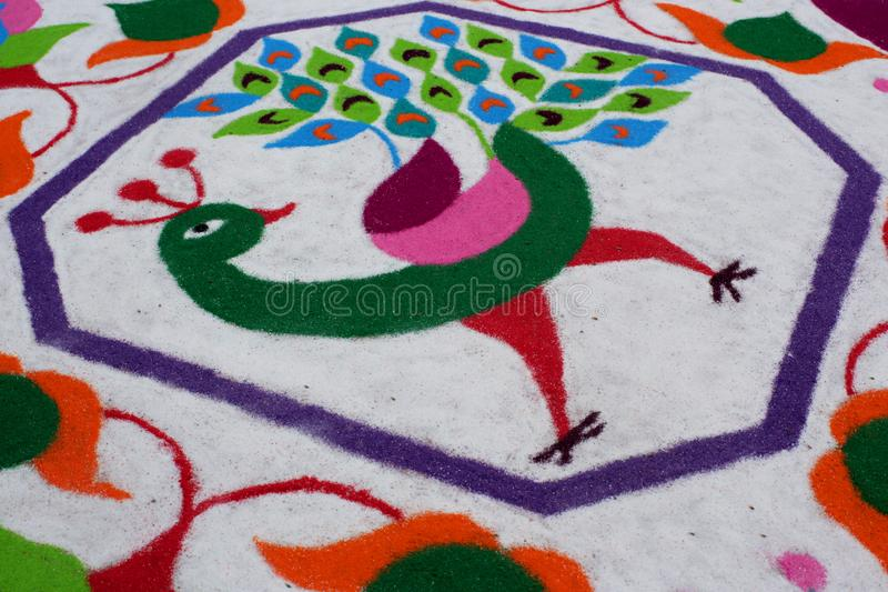 Colourful Rangoli Traditional Floral Design made with Dry Powdered Colours with Peacock, Flowers and Butterflies. A Corner Detail of Colourful Rangoli royalty free stock photo