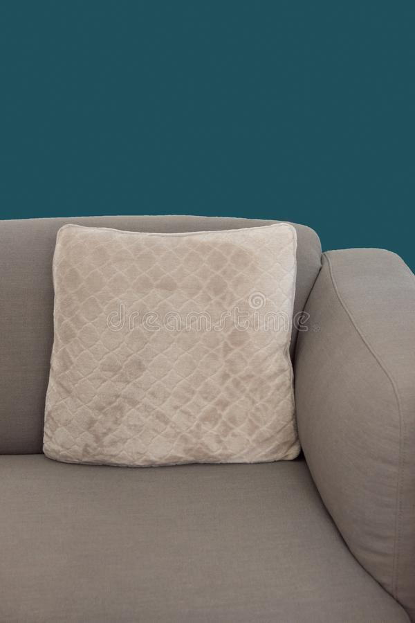 Corner fragment of beige grey upholstered couch with velour decorative cushion on navy blue wall background.  royalty free stock photos