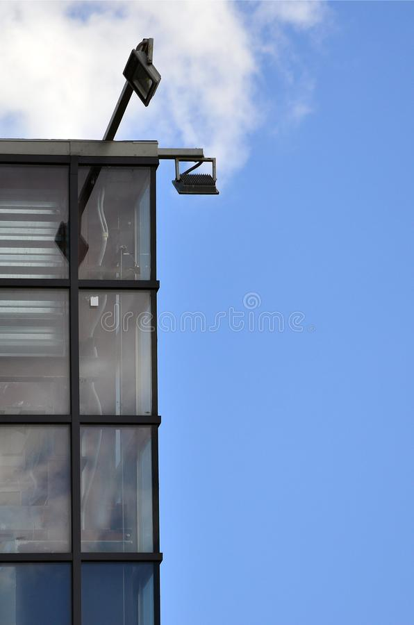 The corner of the glazed office building with the built-in modern street lam. P stock photos