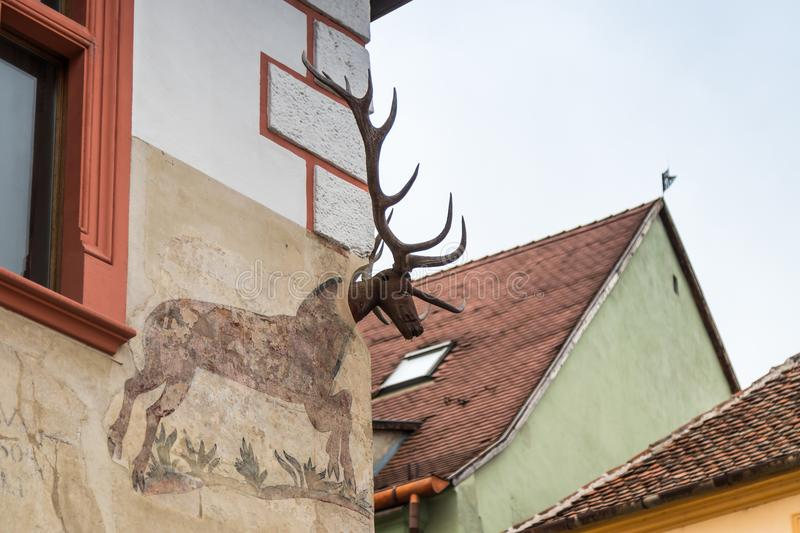 The corner of the house decorated with a decorative chandelier in the castle of old city. Sighisoara city in Romania royalty free stock images