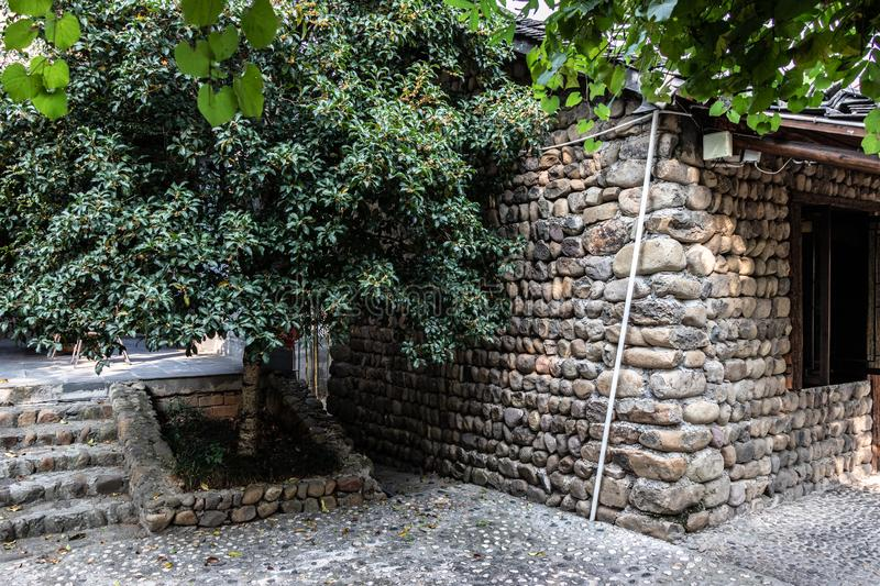 The corner of the house is made of natural cobble stone. Ladder from a natural stone, a protection for a green bush. stock photos