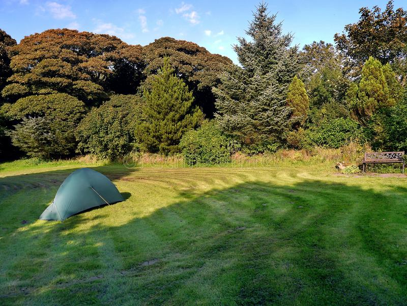 Large garden area with tent. Corner of large garden area surround by trees and a camping tent on the grass royalty free stock photos