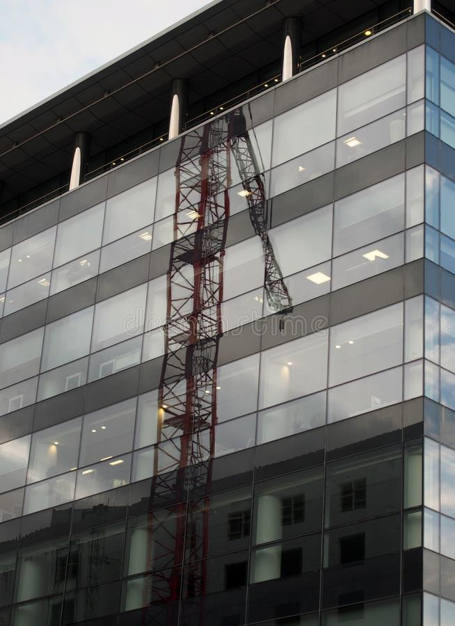 The corner of a modern glass and black office building with reflection of a construction crane on the windows and blue sky royalty free stock image