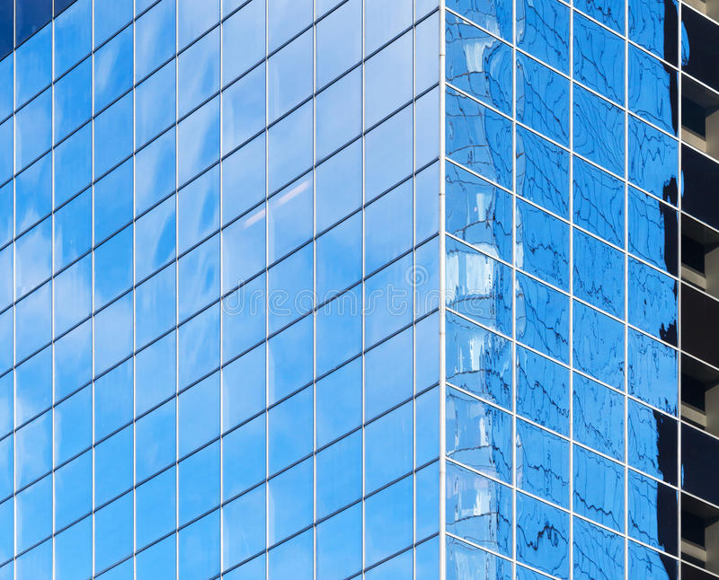 Corner of modern office building. With bright blue sky reflections in windows stock image