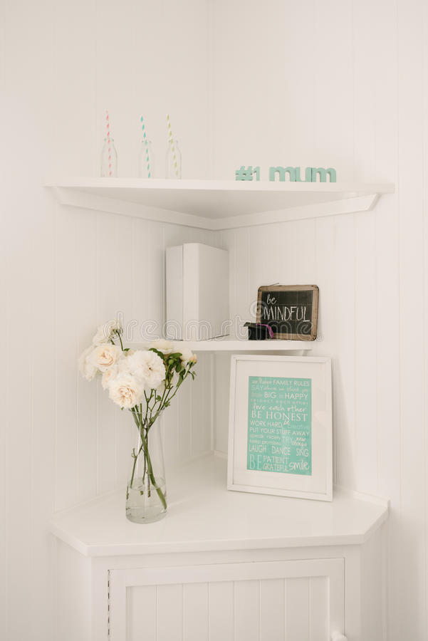 Corner nook in a home office, with white walls. A shelf nook in a home office with a photo frame, flowers, folders and a chalkboard with a written message, very stock photos