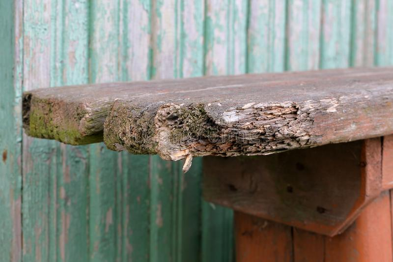 The corner of the old broken board on the bench is covered with moss royalty free stock images