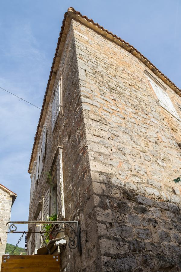 The corner of an old stone house. High building view from below. Old Town of Budva. Montenegro royalty free stock image