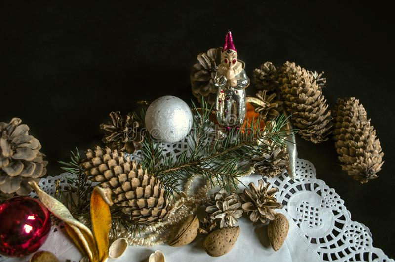 Corner openwork paper napkin with various coniferous cones, coniferous twig, Christmas toys, almonds and orange peels on black ba royalty free stock photography