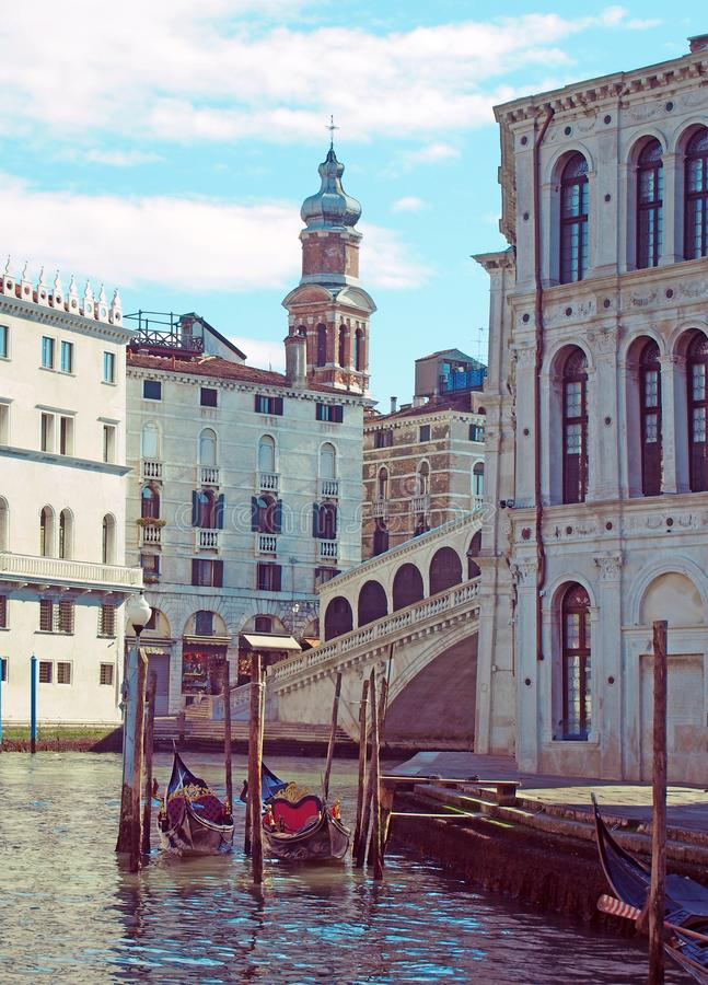 A corner the rialto area of central venice on a sunlit morning with gondolas moored next to the grand canal and old buildings. Surrounding the famous bridge royalty free stock image