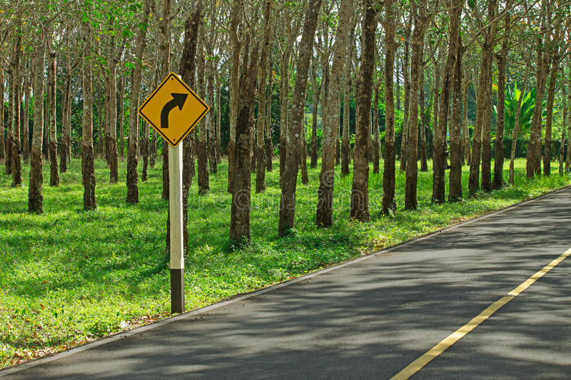 Corner in the road with sign and rubber trees in quaint rural to royalty free stock images