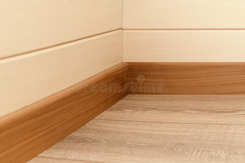 Corner of the room with walls, baseboards and wood floor. Corner of the room with walls, baseboards and natural wood floor royalty free stock photo