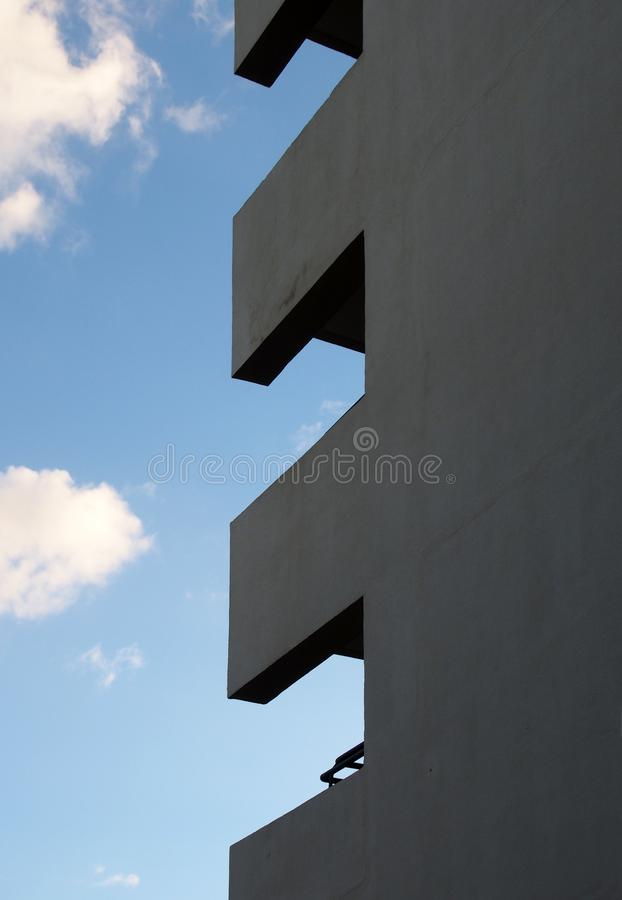 Corner of a tall apartment building with balconies forming geometric shapes against a blue cloudy sky. The corner of a tall apartment building with balconies stock images