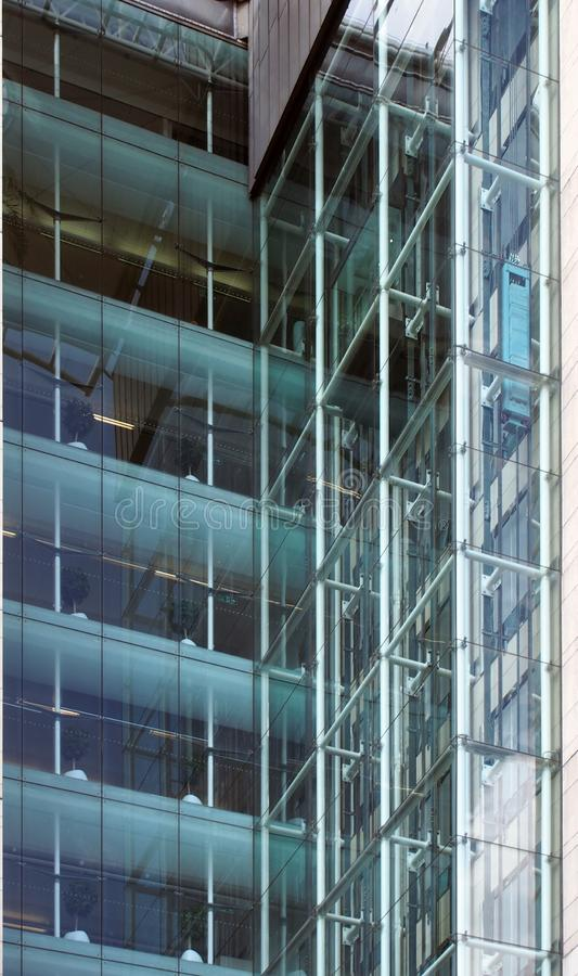 Corner view of elevators and stories in a tall modern glass corporate building with walls reflected in the windows royalty free stock photos
