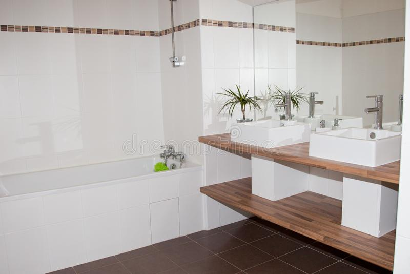 Corner of a white bathroom interior with a wooden floor a double sink and a white. Tub stock images