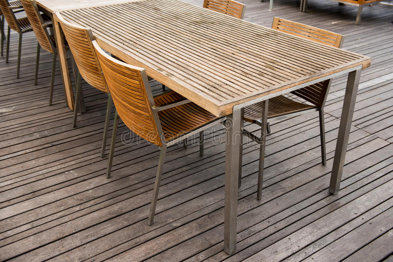 Corner of wood table and chair set. Furniture design. Corner of wood table and chair set on wooden plank floor in outdoor restaurant. Close up stock photos