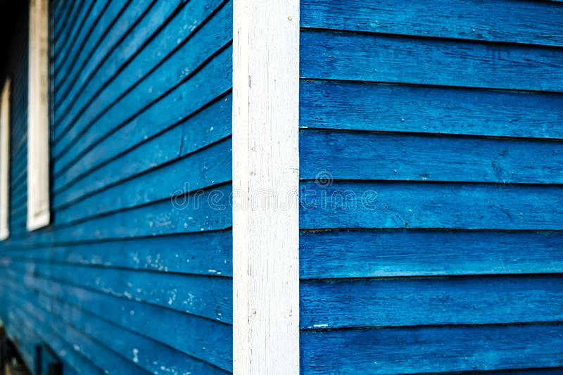 Corner of an wooden house trimmed with boards and painted in bright blue and white royalty free stock photo